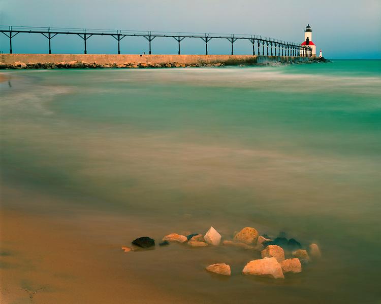 Sunrise glow on the Michigan City Pier Head Lighthouse and Lake Michigan; Michigan City, IN