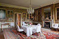 16th century paintings hang from mid-19th century patterned wallpaper designed by Thomas Willement in the family dining room,