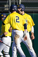 Michigan Wolverines outfielder Jackson Glines (27) celebrates with teammate Jacob Cronenworth (2) after both scored in the first inning of the NCAA season opening baseball game against the Texas State Bobcats on February 14, 2014 at Bobcat Ballpark in San Marcos, Texas. Texas State defeated Michigan 8-7 in 10 innings. (Andrew Woolley/Four Seam Images)