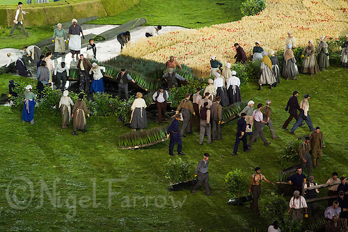 """27 JUL 2012 - LONDON, GBR - Actors playing farmworkers begin to tear up the rural scenery and props at the start of the """"Pandemonium"""" section of the Opening Ceremony of the London 2012 Olympic Games in the Olympic Stadium in the Olympic Park, Stratford, London, Great Britain (PHOTO (C) 2012 NIGEL FARROW)"""