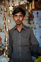 India, Gujarat, Bhuj. Man selling bells in the market.