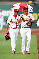 Springfield Cardinals Magneuris Sierra (29) and Alex Mejia (4) walk to the dugout under an umbrella before a game against the Corpus Christi Hooks on May 31, 2017 at Hammons Field in Springfield, Missouri.  Springfield defeated Corpus Christi 5-4.  (Mike Janes/Four Seam Images)