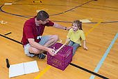 MR / Schenectady, NY. Zoller Elementary School (urban public school). Kindergarten inclusion classroom. Gym teacher commends student for her efforts during physical education assessment to test flexibility. MR: Mel16, Stu1. ID: AM-gKw. © Ellen B. Senisi.
