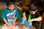 Education preschool 3-4 year olds two boys playing separately side by side at sand table