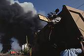 Addis Ababa, Ethiopia<br /> June 4,1991<br /> <br /> Local residence evacuate as an exploding ammunition depot is set alight by former government supporters.<br /> <br /> In late May 1991 the long civil war in Ethiopia came to a climax when the alliance of four rebel groups, the Ethiopian People's Revolutionary Democratic Front (EPRDF), toppled the authoritarian government of Mengistu Haile-Mariam and took control of Addis Ababa and the nation. The governing regime declared a cease-fire and fled. <br /> <br /> In July 1991 the 24 different groups met in the capital and established a multi-party provisional government headed by Meles Zenawi, the Tigray Rebel Leader, to lead the country to its first free elections within two years.