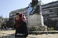 Pictured: A young female migrant walks by a sculpture at Victoria Square Tuesday 23 February 2016<br /> Re: Refugees at Victoria Square in the centre of Athens, Greece