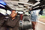 "Catherine, a 32-year- old civil servant rides  the route 46 matatu to work in Nairobi. Solomon Waithaka, the ""conductor"" leans out the open door to coax more passengers."