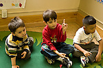 Education preschoool children ages 3-5 group of boys on floor one boy raising finger in asnwer to question horizontal