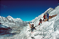 .Porters haul loads up the snout of the Drolambo Glacier with un-named peaks across the Rolwaling Valley in the background. Nepal Himalaya...