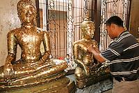 Thaïlande/Bangkok: Au temple de Wat Traimit / Temple du Bouddha d'or - Fidèle appliquant des feuilles d'or en offrande sur les statues de Bouddha
