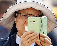 Una suora in attesa dell'inizio dell'udienza generale di Papa Francesco in Piazza San Pietro, Citta' del Vaticano, 17 aprile 2013..A nun takes pictures prior to the start of Pope Francis' weekly general audience in St. Peter's square at the Vatican, 17 April 2013..UPDATE IMAGES PRESS/Isabella Bonotto..STRICTLY ONLY FOR EDITORIAL USE