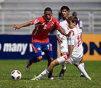 Francisco Narbon (13) of Panama tries to tackle the ball away from John Ruiz (9) of Costa Rica during the quarterfinals of the CONCACAF Men's Under 17 Championship at Catherine Hall Stadium in Montego Bay, Jamaica. Panama defeated Costa Rica, 1-0.