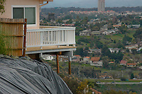 """The deck of a home at the edge of the Mount Soledad landslide hangs precauriously in the air, Monday January 21 2008.  Attorneys for the homeowner allege that the home was further damaged by new movement at the site on Thursday last which their geologists say was caused when city crews graded the bottom or """"toe"""" of the landslide area."""