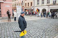 """Rechte demonstrieren in Bautzen gegen Fluechtlinge.<br /> Am Sonntag den 18. September 2016 versammelten sich im saechsischen Bautzen ca. 120 Rechte zu einem Kundgebung mit anschliessender Demonstration um gegen Fluechtlinge zu demonstrieren. Sie riefen Parolen gegen Fluechtlinge und gegen Angela Merkel und beschimpften Medienvertreter als """"Volksverraeter"""".<br /> Nach Aussagen von Anwohnern waren nur etwa 15 Teilnehmer aus Bautzen. Bautzener Rechtsextreme hatten zuvor aufgerufen, sich vorerst nicht an Demonstrationen zu beteiligen, bis ein von ihnen an die Stadtverwaltung gestelltes Ultimatum, zu Loesung der Fluechtlingsfrage verstrichen ist.<br /> Im Bild: Einwohner betrachten verstaendnislos den Aufzug, der schreiend durch die Bautzener Altstadt zieht.<br /> 18.9.2016, Bautzen/Sachsen<br /> Copyright: Christian-Ditsch.de<br /> [Inhaltsveraendernde Manipulation des Fotos nur nach ausdruecklicher Genehmigung des Fotografen. Vereinbarungen ueber Abtretung von Persoenlichkeitsrechten/Model Release der abgebildeten Person/Personen liegen nicht vor. NO MODEL RELEASE! Nur fuer Redaktionelle Zwecke. Don't publish without copyright Christian-Ditsch.de, Veroeffentlichung nur mit Fotografennennung, sowie gegen Honorar, MwSt. und Beleg. Konto: I N G - D i B a, IBAN DE58500105175400192269, BIC INGDDEFFXXX, Kontakt: post@christian-ditsch.de<br /> Bei der Bearbeitung der Dateiinformationen darf die Urheberkennzeichnung in den EXIF- und  IPTC-Daten nicht entfernt werden, diese sind in digitalen Medien nach §95c UrhG rechtlich geschuetzt. Der Urhebervermerk wird gemaess §13 UrhG verlangt.]"""