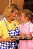 Mother and Daughter baking cookies in the home kitchen having fun
