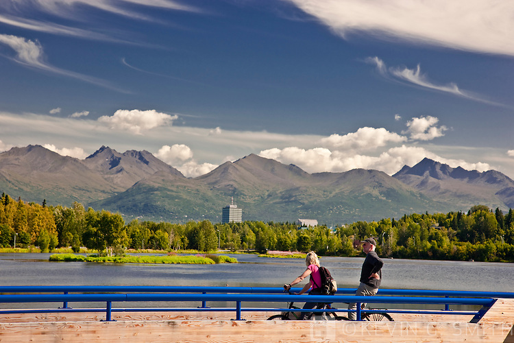 View over the Westchester lagoon, Tony Knowles Coastal Trail and fish viewing platform in the foreground, Chugach Mountains in  the background, summer, Southcental Alaska, USA.Not Model Released