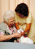 Pet therapy used to engage senior woman in an assisted living facility.