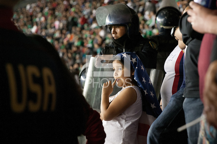 A young USA fan in the American supporters section watches the game while protected by Mexican police at Azteca stadium before the USA vs. Mexico World Cup Qualifier in Mexico City, Mexico on March 26, 2013.
