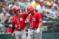 North Carolina State Wolfpack catcher Brett Austin #11 celebrates with outfielder Bryan Adametz #15 during Game 3 of the 2013 Men's College World Series between the North Carolina State Wolfpack and North Carolina Tar Heels at TD Ameritrade Park on June 16, 2013 in Omaha, Nebraska. The Wolfpack defeated the Tar Heels 8-1. (Brace Hemmelgarn/Four Seam Images)