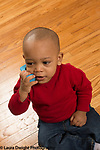 18 month old toddler boy using a block as a telephone, talking