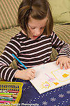 5 year old girl art activity drawing picture with colored pencil or marker talking to herself