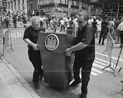 New York City<br /> July 23, 2011<br /> <br /> At the beginning of the annual New York City Gay Pride Parade, two men move a podium where New York's Governor, Andrew Coumo, just announced historical legislation legalizing gay marriage in the State of New York.