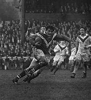 4 Mars 1967. L'équipe de France de rugby à XIII rencontre l'équipe d'Angleterre à Wigan. Cliché pris durant le match ; au 1er plan action de jeu, le joueur toulousain Georges Aillières a le ballon ; en arrière plan tribune du stade Central Park.