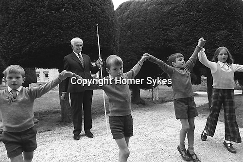 Paniswick Church Clypping Ceremony, Painswick, Gloucestershire, England 1973. September 19th or Sunday following.<br /> <br /> The congregation and children hold hands, in a circle around the whole of the church, if they can, to complete the unbroken circle.