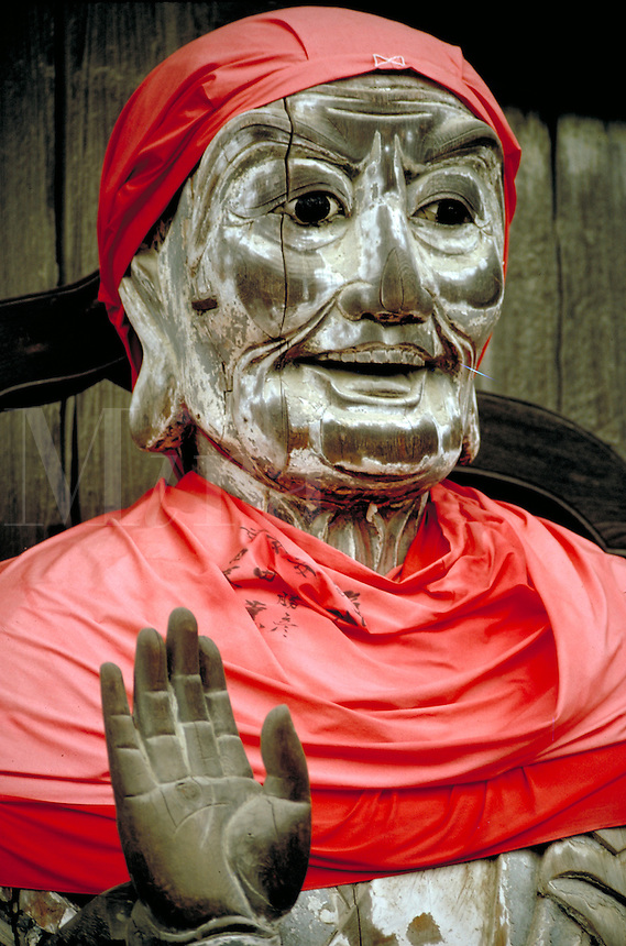 Buddha draped in red at the Nara shrine in Nikko, Japan. Statues of Buddha are often well tended, given red (happy) cloth to wear, protected by parasols and are given offerings of flowers, water and food. Nara, Japan Nikko.