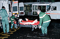 Paramedic ambulance crew taking a patient on a stretcher into a hospital.