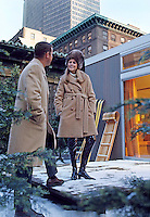 Couple models winter fashion in front of a pre-fab ski house at Abercrombie & Fitch, New York City, 1967. Photo by John G. Zimmerman