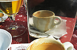 Empty coffee cup and glass of beer at the end of a lunchtime meal Verona Italy