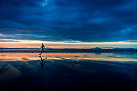 Runner on Harlech Beach during spectacular sunset, North Wales