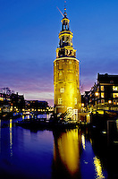 clock tower, canal, Amsterdam, The Netherlands, Holland, Europe, The illuminated clock tower reflects in the calm waters of the canal (grachten) in downtown Amsterdam at night