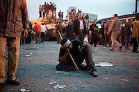 A young anti-government protester sits exhausted on the ground after hours of violent clashes with pro-Mubarak supporters in Tahrir Square. Continued anti-government protests take place in Cairo calling for President Mubarak to stand down. After dissolving the government, Mubarak still refuses to step down from power.