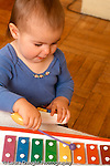 14 month old toddler girl playing with toy musical instrument xylophone Caucasian vertical