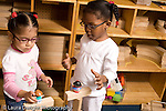 Preschool ages 3-5 two girls building together playing with human figures on top of block structure they made horizontal
