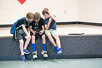 Killian Baldwin (from the left) Parker West and Jaden Becht play a game Monday July 26, 2021 during the lunch break at the Donald W. Reynolds Boys and Girls Club in Fayetteville. The boys are attending the clubs summer program. For information about activities at the club see https://www.fayettevillekids.org/  Visit nwaonline.com/21000727Daily/ and nwadg.com/photo. (NWA Democrat-Gazette/J.T. Wampler)