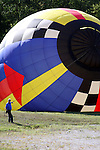 A hot air balloon rising with the hot air and being directed by a safety man