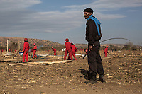 A Red Ants Task Team member (leader), directs a group of his men as they demolish shacks that had been built illegally on private land. The Red Ants are a controversial private security company often hired to clear squatters from land and so-called 'hijacked' properties.