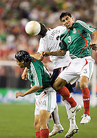 USA's Clint Dempsey heads the ball in between Mexico's Gonzalo Pineda and Carlos Salcido. USA 2, Mexico 0, at the University of Phoenix Stadium in Glendale, AZ on February 7, 2007.