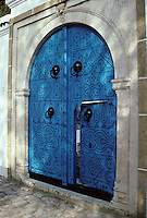 Tunisia, Sidi Bou Said.  Doorway to a Family Courtyard.  The higher pair of door knockers dates from the time guests arrived on horseback.