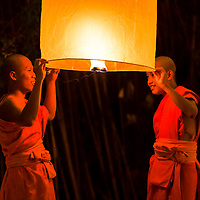 Two traditional novice monks lighting a floating paper lantern during Loy Krathong festival at Wat Phan Tao temple, Chiang Mai Thailand