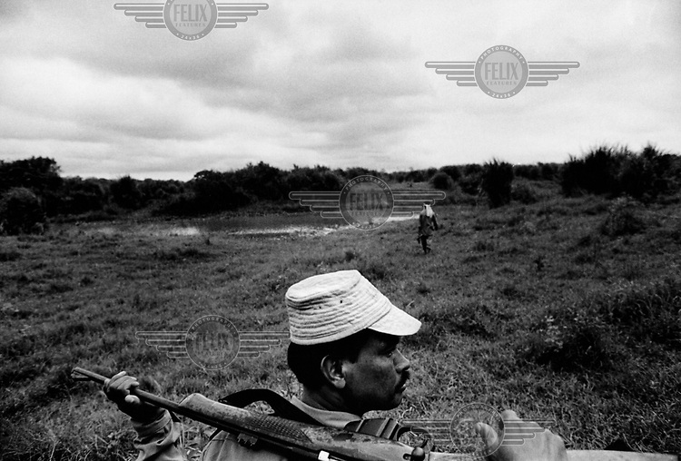 A wildlife ranger carries a rifle on his shoulders while on his afternoon patrol in Kaziranga National Park.
