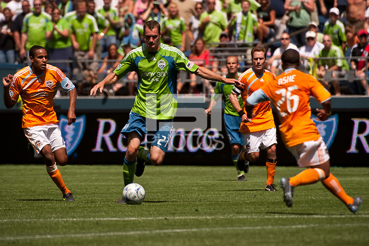 Nate Jacqua (c) of the Seattle Sounders drives past Ricardo Clark (l) and Corey Ashe(r) of the Houston Dynamos in the match at the XBox Pitch at Quest Field on July 11, 2009. The Sounders defeated the Dynamo 2-1.