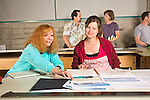 Two young female students discuss landscape drawings at drawing tables in adult education class in evening