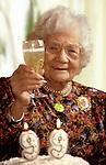 Elderly woman enjoying a glass of Champagne on her 99th birthday