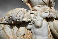 Close up of Roman Sebasteion relief  sculpture of Nero conquering Armenia depicting a fallen female representing Armenia,  Aphrodisias Museum, Aphrodisias, Turkey.   Against a grey background.<br /> <br /> Nero, wearing only a cloak and sword strap, supports a slumped naked Armenia by her upper arms. She wears a soft eastern hat, and her bow and quiver are next to her. The heroic composition likens them to Achilles and the Amazon Queen Penthesilea. The inscription reads: Armenia - (Neron) Klaudios Drousos Kaisar Sebastos Germanikos.