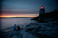 Fisherman cast their lines as Castle Hill Lighthouse glows in the early evening.