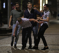 Pictured: Two men (in light shirts) fight, while two other men try to stop them in the early hours of Saturday, 17 December, 2016<br /> Re: Mad or Black Friday in Middlesbrough, England, UK